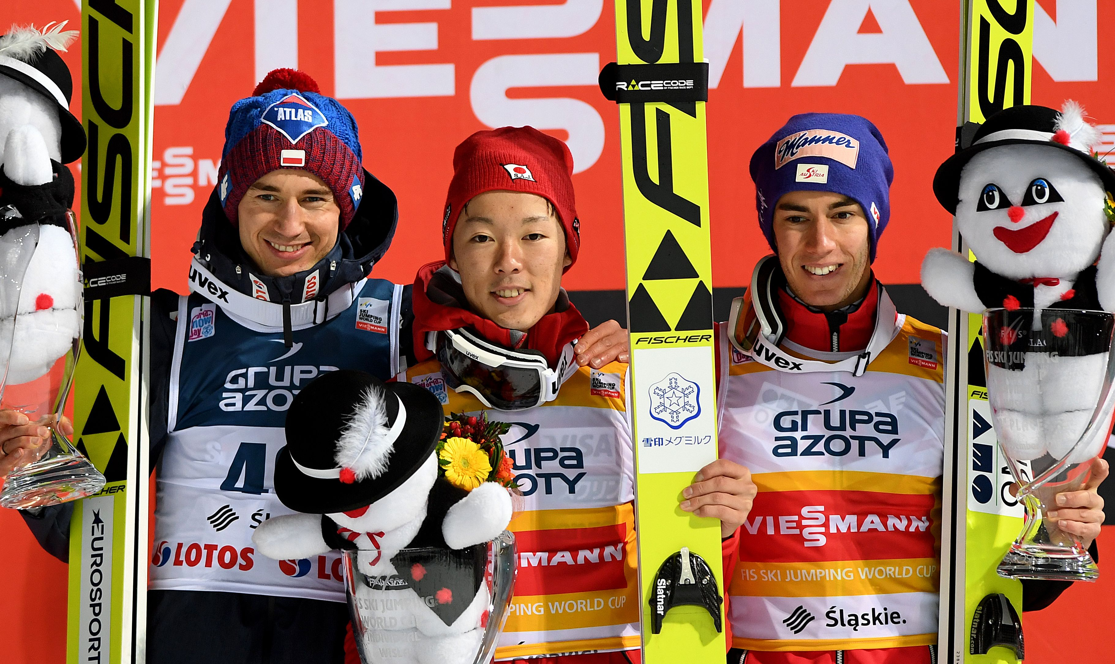 (L-R) Kamil Stoch of Poland second place, Junshiro Kobayashi of Japan first place and Stefan Kraft of Austria, third place pose at the podium after the FIS Ski Jumping World Cup in Wisla, Poland on November 18, 2017. Junshiro Kobayashi of Japan won the competition ahead of Poland's Kamil Stoch (2nd) and Austria's Stefan Kraft (3rd). / AFP PHOTO / JANEK SKARZYNSKI